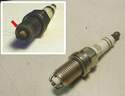 In the photo inset, you can see an unusual spark plug with all four of its electrodes eaten away (red arrow).
