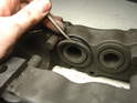 Remove the outer seal by simply prying it out of the caliper housing.