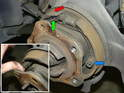 Using a pair of pliers, grab and unhook the parking brake spring from the brake shoes (green arrow).