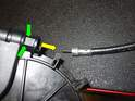 Insert a small flat blade screwdriver (green arrows), and gently pry upward while pulling the cable out (yellow arrow) of the housing.