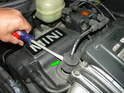 Use a screwdriver to gently pry the spark plug boot up off the spark plug and out of the cylinder head (Green arrow)