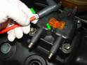 The new spark plug wires will have a plastic tab mounted around it to indicate which cylinder it goes to (green arrow).