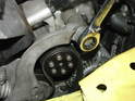Now remove the long 16mm bolt securing the tensioner arm to the engine at the front as shown here.