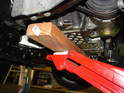Place the floor jack under the center of the engine with a block of wood to distribute the weight of the engine and also to protect the oil pan.