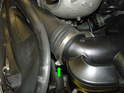 Loosen the hose clamp securing the plastic lower air feed hose to the scoop on the radiator shroud (green arrow).