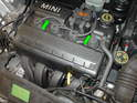 On Cooper models, open the hood and release the two clips holding the fuel rail cover to the fuel rail (green arrows) and pull the cover off.