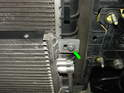 Remove the 10mm bolt securing the right side of the A/C condenser to the radiator frame (green arrow).