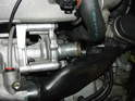 The upper hose is routed in between the water pump and the air bypass valve.