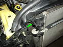 Remove the retaining pins at each side of the top of the radiator (green arrow).