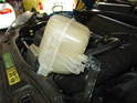 (R55/R56/R57 Cooper and Cooper S):Rotate the tank up and out of the engine bay.