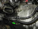 Remove the mounting bolt on the front of the engine which also holds the bracket for the alternator wiring and let the harness hang free (green arrow).