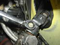 Move over to the driver's side of the car and remove the nut and bolt holding the steering rack to the steering column.