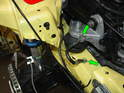 On the passenger side of the car, remove the two 10mm nuts that secure the ground strap from the frame rail to the engine mount (green arrows).
