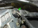 On the back of the alternator, press the tab on the connector and pull the plug out of the back of the alternator (green arrow).