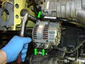 Now remove the three mounting bolts holding the alternator to the engine block (green arrows) and carefully remove the alternator from the engine.
