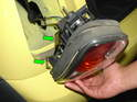 Once the nut is removed, carefully pry the taillight assembly out of the body.