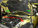 The green arrows show the two hood shocks.