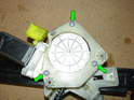 Remove the three T20 Torx screws securing the upper motor frame and motor to the regulator gearbox (green arrows).