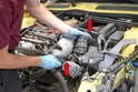 Begin by using a flathead screwdriver and loosening the two hose clamps (red arrows) that connect the intake tube from the air box to the throttle body and lift the tube out.