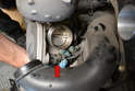 Disconnect the wiring harness by squeezing the tab and pulling it straight back off the throttle body (red arrow).