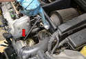 Use a 10mm socket and extension and remove the four bolts holding the throttle body on (red arrow).