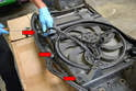 Disconnect the fan wiring harness from the front clip using a panel popper or flathead screwdriver (red arrows).