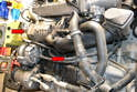 Next use a 10mm socket and remove the two bolts holding the dipstick and tube to the engine (red arrows).