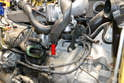 Use a set of pliers and remove the hose from the front of the water pump (red arrow).