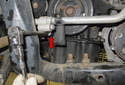Working at the A/C line, remove the 10mm fastener (red arrow).