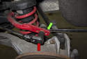 Rear sway bar links: Working at the sway bar, loosen the 16mm end link nut (red arrow) while counter-holding the ball joint with a 16mm wrench (green arrow) or vise grips.