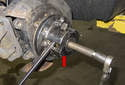 Using an axle removal tool (red arrow), press the front drive axle out of the wheel hub.