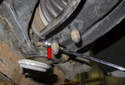 Once free, remove the nut with the open-end of your wrench (red arrow).