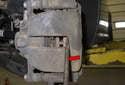 Using a flathead screwdriver (red arrow), slowly press the brake caliper piston in.