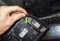Flip the trim panel over and disconnect the electrical connector (green arrow) by pulling it straight out.