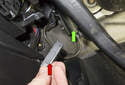 This photo shows the clutch switch (red arrow) being removed from the clutch master cylinder (green arrow).