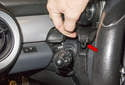 Pull the upper steering column trim cover off the steering column, detaching the clips (red arrow).
