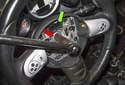 Using a breaker bar with a 16mm socket, remove the steering wheel center bolt (red arrow).
