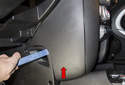 Working at the side of the lower instrument panel, use a plastic prying tool and remove the cover (red arrow).