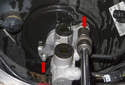 Using a 13mm universal socket on a long extension, remove both master cylinder nuts (red arrows).