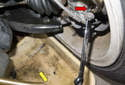 Install a box wrench on the bleeder screw (red arrow).