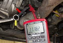 Testing with sensor removed: In this photo the wrench (yellow arrow) is close to the sensor (red arrow), so the DVOM reads 12 volts.