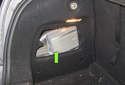 The amplifier (green arrow) is mounted in the left rear fender area, behind the carpeted trim panel.