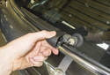 Working at the wiper arm pivot, open the plastic cap.