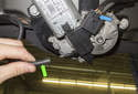 Working at the wiper motor, remove the washer fluid hose by pulling it straight off (green arrow).