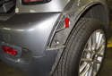 Next, remove the Phillips head screw at the upper corner of the bumper cover (red arrow).