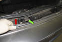 Lift up (red arrow) and detach the bumper cover from the center mount (green arrow).