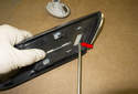 Side Marker Bulb: To replace the emblem, lever up the locking clip on the backside of the mounting bracket (red arrow).