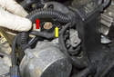 Pull the coil wiring harness (red arrow) up and place it behind the vacuum nipple (yellow arrow).