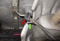 Working at the muffler, detach the rubber insulators (red arrow) by levering them off using a pry bar (green arrow).