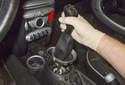 Next, remove the shift knob by it pulling straight up and off the shift lever (red arrow).